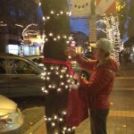 Volunteer Liam helps to hang scarves along Washington Street