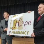 Lester Burris, at left, and J.T. Doane unveil the sign for the new Hope Wellness Pharmacy.